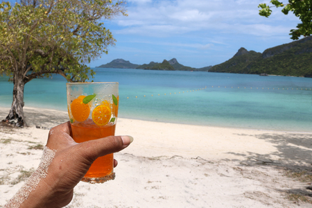 Glass of orange juice on the beach with views of the archipelago Islands,Thailand