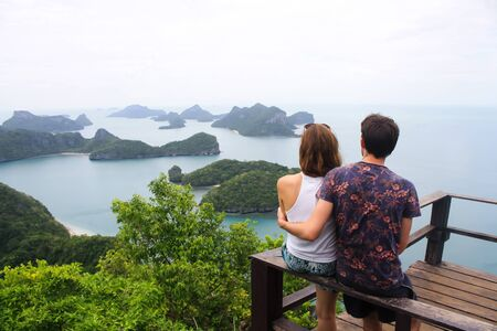 Man and woman sitting on top of a mountain and looking the view at angthong island