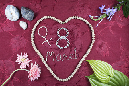 greeting cards International Women s Day: Stone, leaves, flowers, seeds and silver necklace with Red Background - 8 March International Happy Womens Day greeting card.