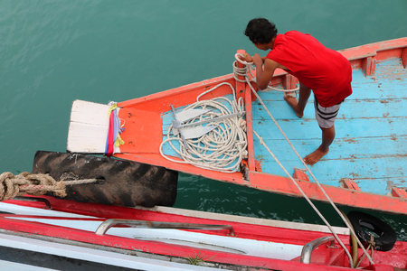 boat crew: Crew are using a rope tied into a small boat with a big boat in Thailand