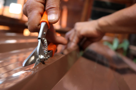 Workers use scissors to cut the metal sheet for roofing. Stock Photo