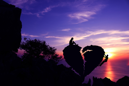 Women sit and man climbing on broken heart-shaped stone on a mountain with purple sky sunset background.Silhouette Valentine background concept. Stock Photo