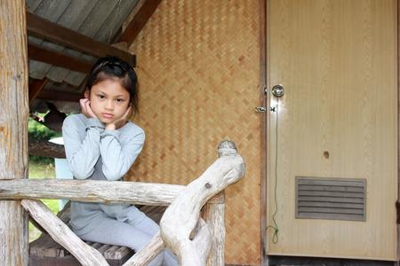 sadly: Asian girls sitting sadly on the old house balcony.