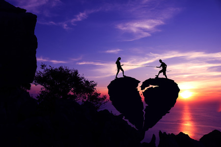 Couples pulling a rope on broken heart-shaped stone on the mountain with purple sky sunset background.Silhouette Valentine background concept.