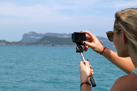 European girl tourists enjoy the GoPro camera and view of the island and the sea on the boat. Stock Photo