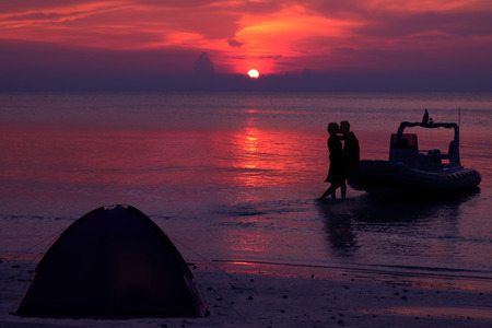 dinghies: Silhouette couple kissing and camping on the beach with dinghies private boat and purple sky sunset background. Stock Photo