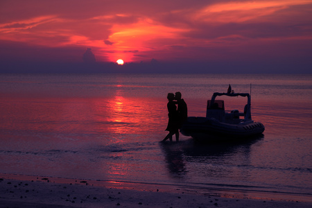dinghies: Silhouette couple kissing on the beach with dinghies private boat and purple sky sunset background Stock Photo