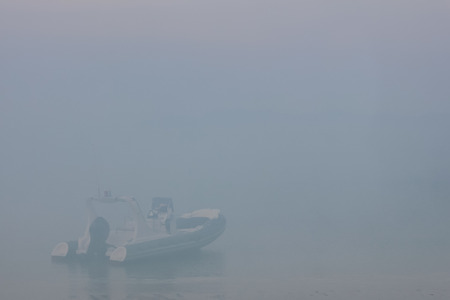 dinghies: Blurred dinghies boat in the fog-covered sea. Stock Photo