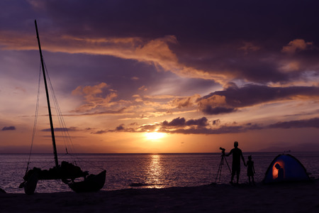 dinghies: Silhouette family camping on the beach with sailboat and purple sky sunrise background.
