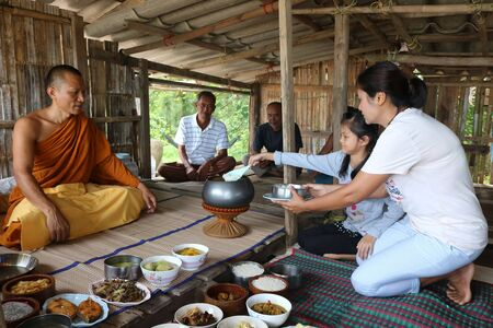 local 27: Local people are offering food to the monks in the bamboo hut at fishermans Village, Samui, Thailand April 27, 2017