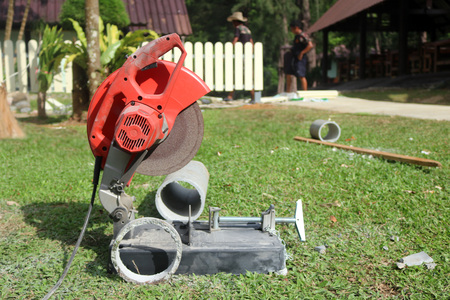 fibra de vidrio: Electric circular saw cutting the cement pipe in the garden.