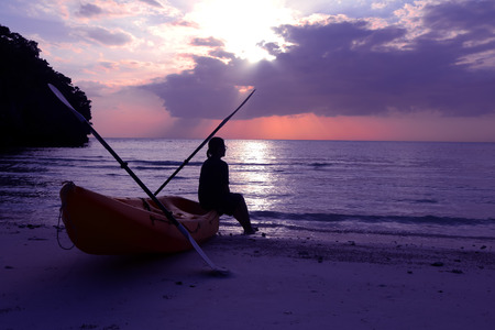 daybreak: Silhouette kayaking on the beach with tourist girl looking blue sky sunset.