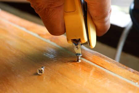 Tightening the screw by mag stapler to fix the problem. Stock Photo