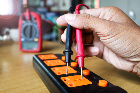 Electricians worker use voltmeter measure the current from extension cord sets plug. Stock Photo