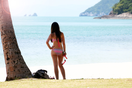 Tourist girl with a diving mask on the snorkeling area near the beach.Samui island Thailand.