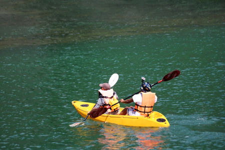 Tourists with cameras recorded video on the head are enjoy kayaking in the sea. Stock Photo