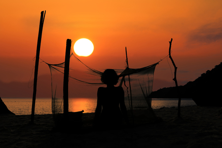 Silhouette of a woman camping alone on the beach with mosquito net, Red sky sunset background.