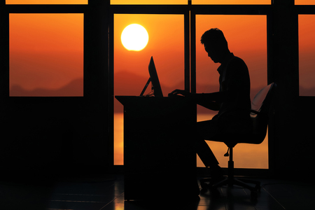 Silhouette asian business man working on a computer in the evening with sunset background. Banco de Imagens