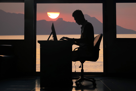 Silhouette asian business man working on a computer in the evening with sunset background. Banque d'images