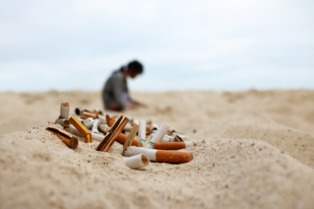 Zigaretten- und Tabakaschenbecher am Strand. Freiwilliges Mädchen, das Kolben und Abfall auf dem Sand sammelt. Destruktive Natur der Marineverschmutzung