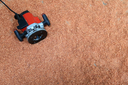 Electric circular routering saw on the sawdust in the floor of the factory
