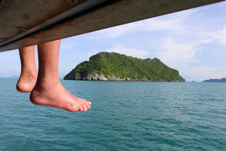 Feet of traveller on the tour boat , People sitting on the boat and traveling around the island and the sea in Thailand