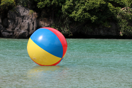 Large colorful beach balls on the water in the sea by the beach in Thailand