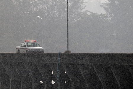 Police cars were running on the bridge while heavy rain in Thailand