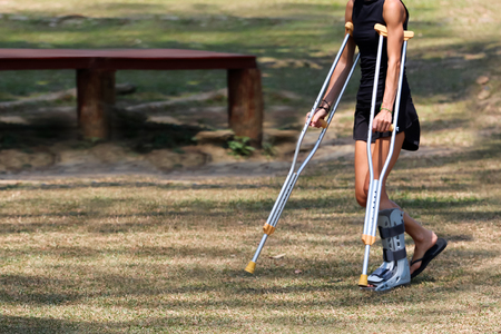 Accident tourist girl are walking by crutches in the garden.Travel in Thailand