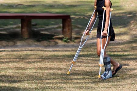 Unfalltouristisches Mädchen gehen durch Krücken im Garten. Reise in Thailand
