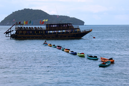 Asian guide paddle by towing the kayak and tied together in a row back to the big boat.Raining season in Thailand