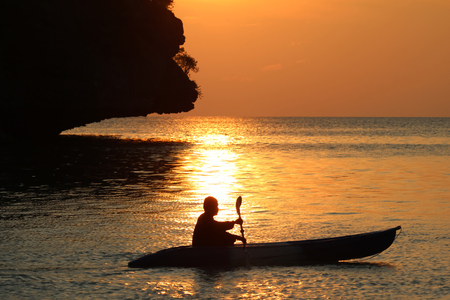Asian man rowing a kayak near the beach with red sky sunset background. Stock Photo