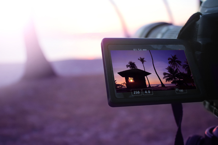 The camera with flip screen  while recording a video view of the sunrise on the coconut beach. 스톡 콘텐츠