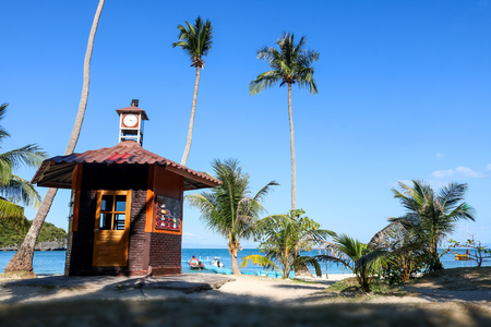 The clock tower on the coconut beach. Lifeguard tower , Hut or Cottage against the blue sky and ocean background. Stock Photo