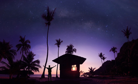 Panoramic landscape of man standing on the coconut beach with a million stars and sunrise early morning. Stock Photo