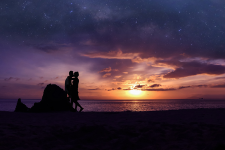 Silhouette couple kissing on the beach  with million stars galaxy and purple sky sunrise background