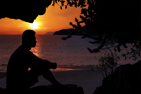 Man sitting in a cave near the beach with the sunrise in the morning. Reklamní fotografie