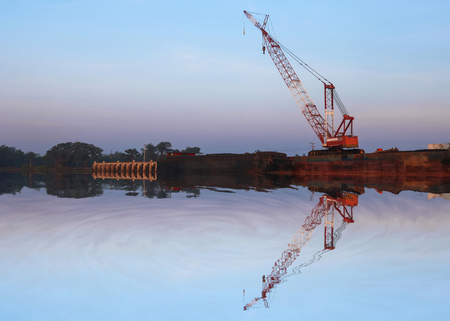 Mirror reflection of Crawler cranes used for rebuilding bridges  near the river in Thailand