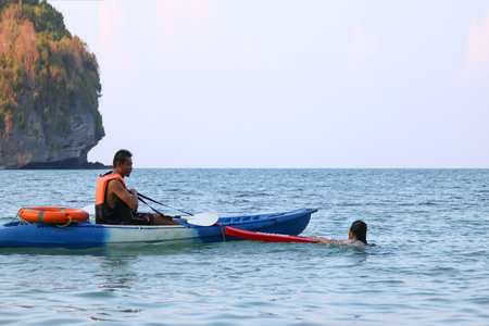 Asian father and daughter are teaching and training life guard or rescue on the beach in the evening.