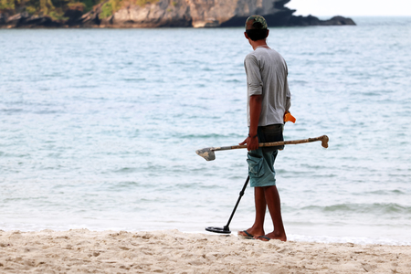 Asian male uses metal detector to find objects on a beach in Thailand