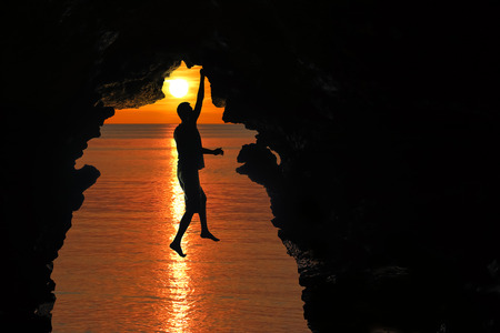 Man climbing in the cave by the sea with red sky and sunset background