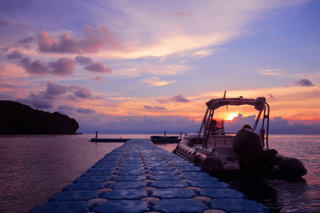 Rubber boat or dinghy dock on the floating pier early morning beautiful sunrise background. Stock Photo