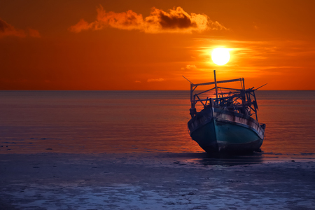 Old broken boat abandoned on the beach at sunset ,Red sky background
