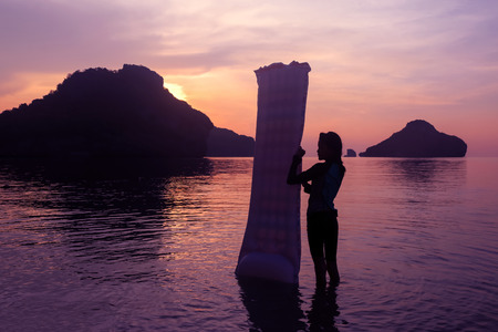 Asian girl enjoying with inflatable raft on the beach at sunset, Red sky background at Archipelago island in Thailand.