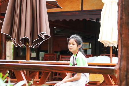 Asian girl working in the restaurant during the summer, Child labor was cleaning in the restaurant in Thailand. Фото со стока