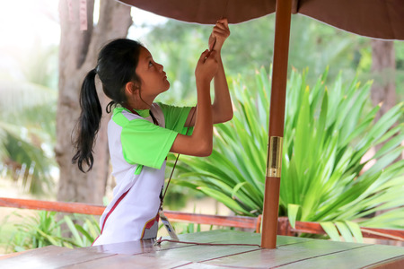 Asian girl raise an umbrella, Students or Children working in the restaurant during the summer in Thailand.
