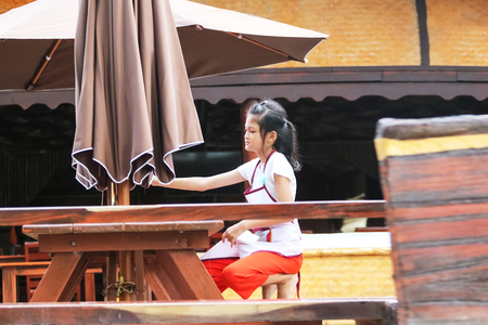 Asian Students ,Children working in the restaurant during the summer, Child labor was cleaning in the restaurant.The girl was pulling a large umbrella.