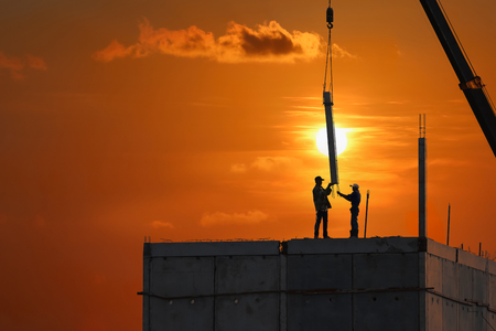 Silhouette construction workers are working on top of building structure with sunrise sky background