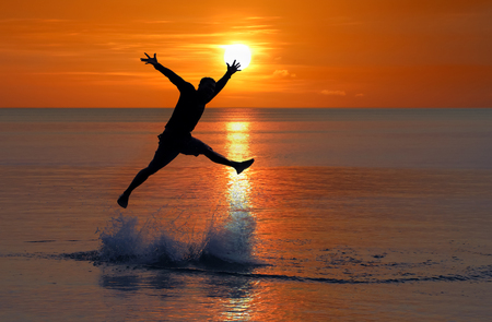 Man jumped up from the sea near the beach at sunset red sky background
