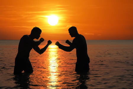 Asian man practicing Thai boxing on the sea beach at sunset.Thailand Фото со стока